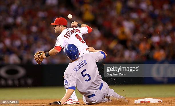 Second baseman Taylor Featherston of the Los Angeles Angels of Anaheim can't turn a double play as he loses control of the ball as he transfers it to...