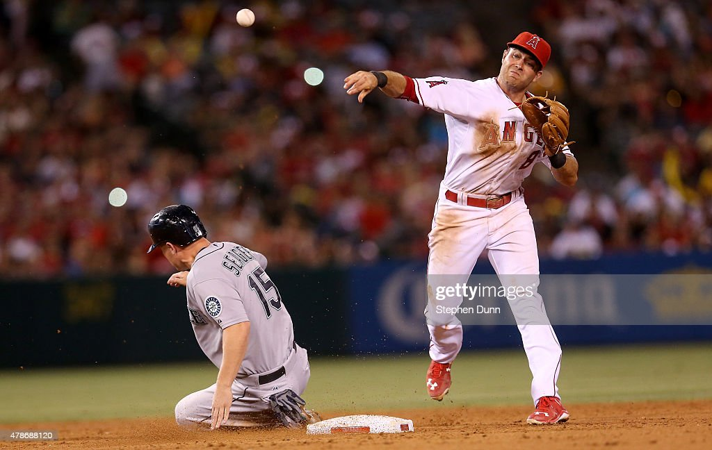 Second baseman Taylor Featherston #8 of the Los Angeles Angels of Anaheim throws to first to complete a double play after forcing out Kyle Seager #15 of the Seattle Mariners in the sixth inning at Angel Stadium of Anaheim on June 26, 2015 in Anaheim, California.