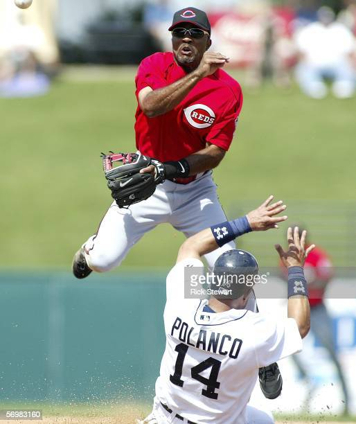 Second baseman Tony Womack of the Cincinnati Reds turns a double play as Placido Polanco of the Detroit Tigers slides into second base during a...