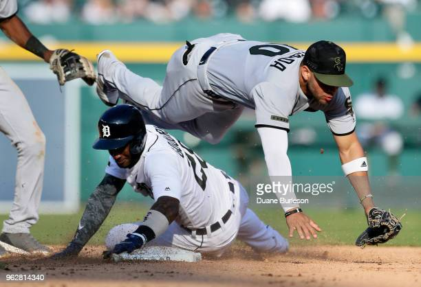 Second baseman Yoan Moncada of the Chicago White Sox tumbles over Niko Goodrum of the Detroit Tigers after turning the ball at second base during the...