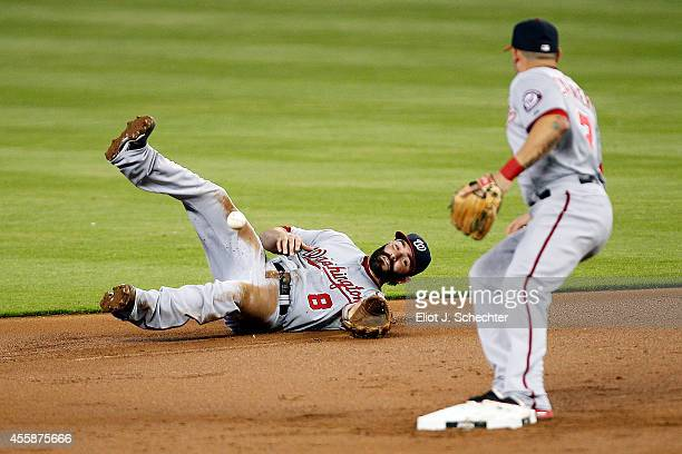 Second basemen Danny Espinosa of the Washington Nationals has difficulty getting the ball to teammate Asdrubal Cabrera against the Miami Marlins in...