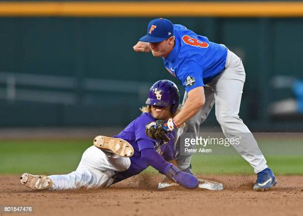 Second basemen Deacon Liput of the Florida Gators tags out base runner Kramer Robertson of the LSU Tigers attempting to steal second base in the...
