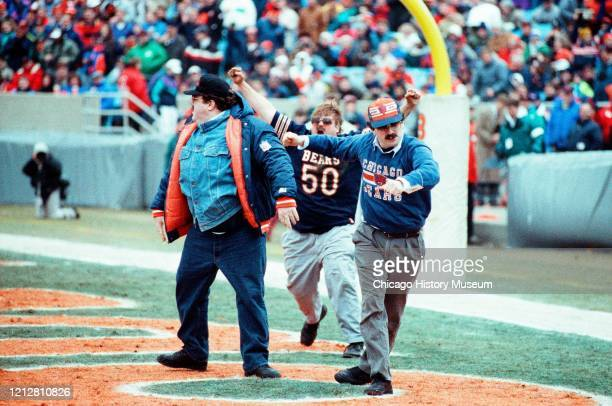 Second City alumni George Wendt and Chris Farley clown around at a Chicago Bears game at Soldier Field 1410 Museum Campus Drive Chicago Illinois...