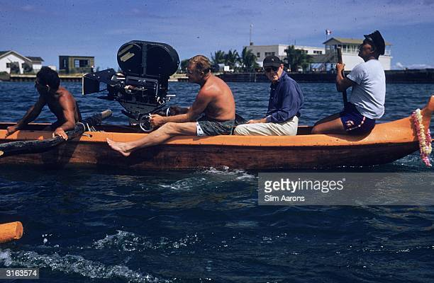 Second from right codirector John Ford in a rowing boat with cameraman and crew during the filming of 'Mister Roberts'