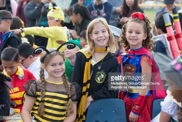 Second grade classmates Addison Mrosek left Emily Gritchen center and Brooke Bantle are all smiles as they watch the annual Halloween Parade at...