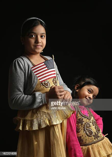 Second grade student Maria Rahman born in Bangladesh holds a flag given to her by the US Citizenship and Immigration Services while waiting to...