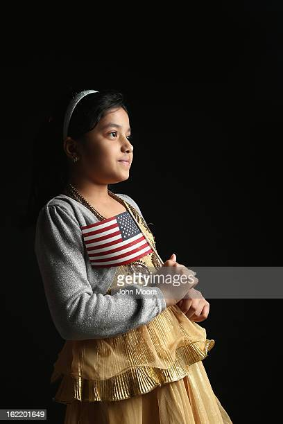 Second grade student Maria Rahman holds a flag given to her by the US Citizenship and Immigration Services while waiting to receive her citizenship...