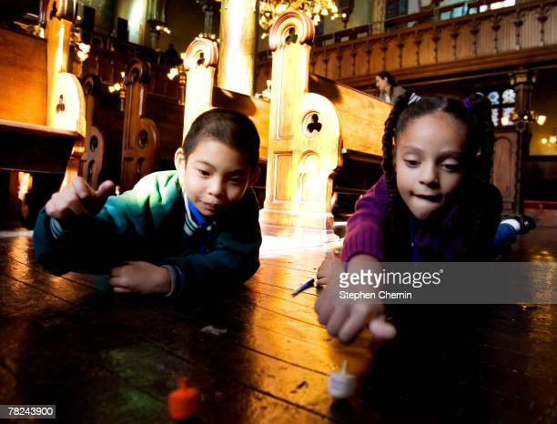 PS 1 second grade students Jeffrey Ng and Nimue Wise spin dreidels December 4 2007 at the Eldridge St Synagogue in New York City The class was there...