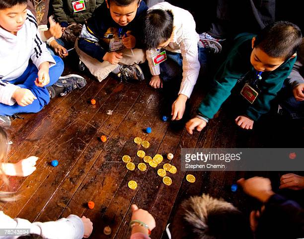 PS 1 second grade students play with dreidels and chocolate gold coins after lighting the menorah December 4 2007 at the Eldridge St Synagogue in New...