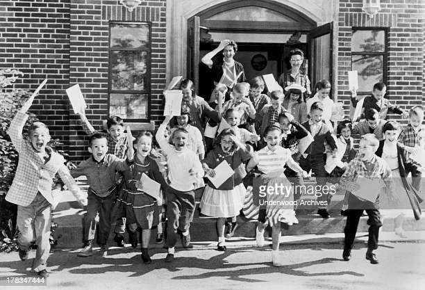 Second graders rush out the door on the last day of school while their teacher bids them goodbye, Mt. Carmel, Ohio, c. 1963.
