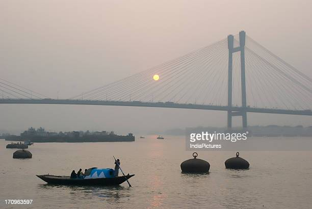 Second Hooghly Bridge or Vidyasagar Setu at sunset with boats on the river Hooghly Kolkata West Bengal India