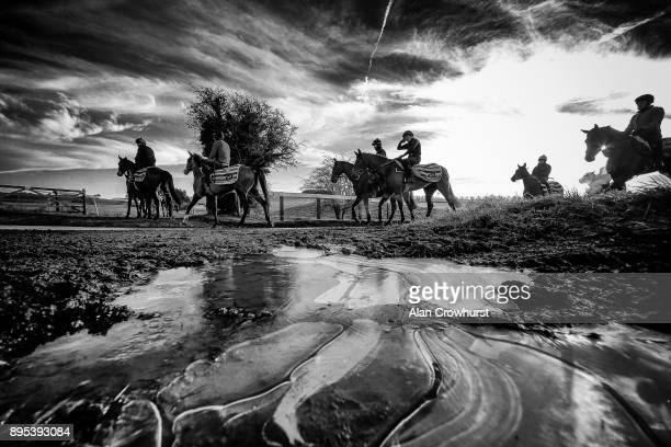 Second lot leave the yard and head for the gallops passing frozen puddles at Nicky Hendersons Seven Barrows stables on December 19 2017 in Lambourn...