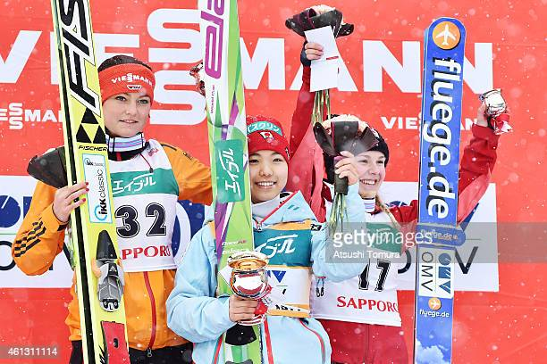 Second place Carina Vogt of Germany, first place Sara Takanashi of Japan and third place Chiara Hoelzl of Austria pose in the victory ceremony during...