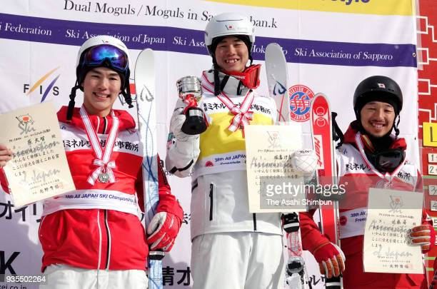 Second place Daichi Hara winner Ikuma Horishima and third place Sho Endo pose on the podium at the medal ceremony for the Men's Dual Mogul on day one...