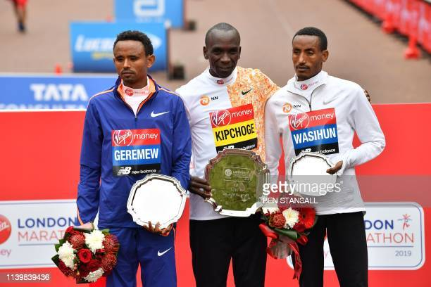 Second place Ethiopia's Mosinet Geremew winner Kenya's Eliud Kipchoge and third place Ethiopia's Mule Wasihun pose for a photograph at the medal...
