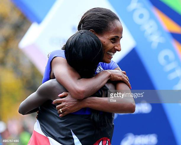 Second place finisher Aselefech Mergia of Ethiopia hugs first place finisher Mary Keitany of Kenya after she crossed the finish line during during...