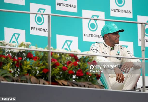 Second place finisher Lewis Hamilton of Great Britain and Mercedes GP looks dejected on the podium during the Malaysia Formula One Grand Prix at...