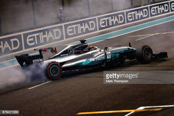 Second place finisher Lewis Hamilton of Great Britain and Mercedes GP celebrates with donuts on track during the Abu Dhabi Formula One Grand Prix at...