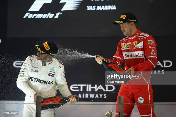 Second place finisher Lewis Hamilton of Great Britain and Mercedes GP celebrates with third place finisher Sebastian Vettel of Germany and Ferrari on...
