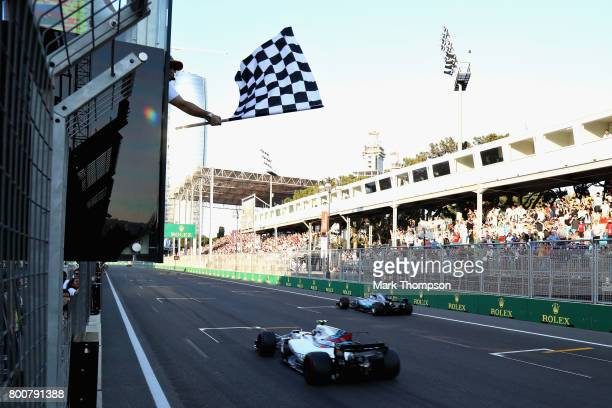 Second place finisher Valtteri Bottas driving the Mercedes AMG Petronas F1 Team Mercedes F1 WO8 crosses the line ahead of third placed Lance Stroll...