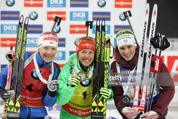 Second place Kaisa Makarainen of Finland first place Laura Dahlmeier of Germany and third place Anais Bescond of France celebrate during the flower...