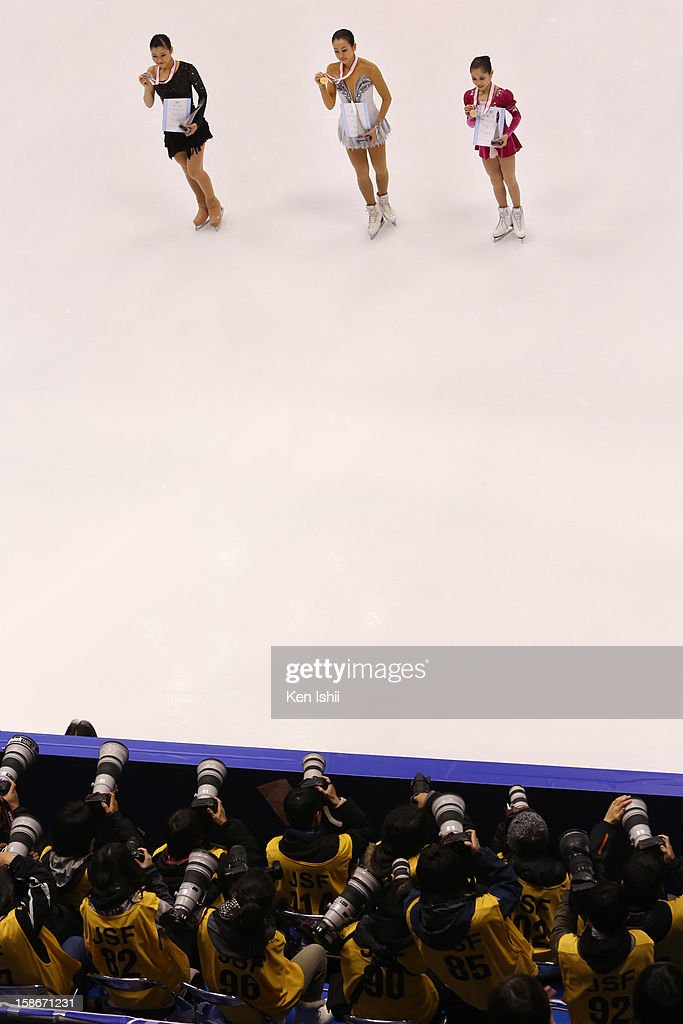 Second place Kanako Murakami, first place Mao Asada, third place Satoko Miyahara pose for photographs during day three of the 81st Japan Figure Skating Championships at Makomanai Sekisui Heim Ice Arena on December 23, 2012 in Sapporo, Japan.