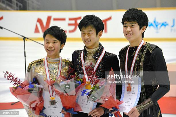 Second place Kazuki Tomono winner Sota Yamamoto and third place Daichi Miyata pose on the podium at the medal ceremony for the Men's Singles during...