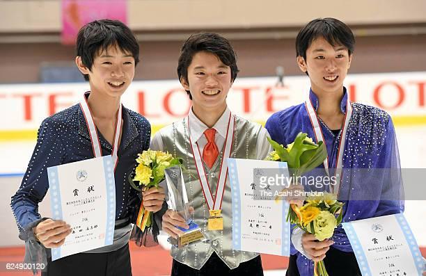 Second place Koshiro Shimada winner Kazuki Tomono and third place Mitsuki Sumoto pose on the podium at the medal ceremony for the Men's Singles...