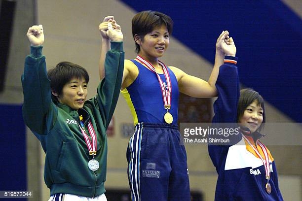 Second place Kumie Matsumiya, first place Mari Nakaga and third place Hiromi Miyake celebrate on the podium at the medal ceremony for the -53kg...