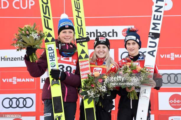 Second place Maren Lundby of Norway, first place Chiara Hoelzl of Austria and third place Eva Pinkelnig of Austria stand on the podium on FIS Ski...
