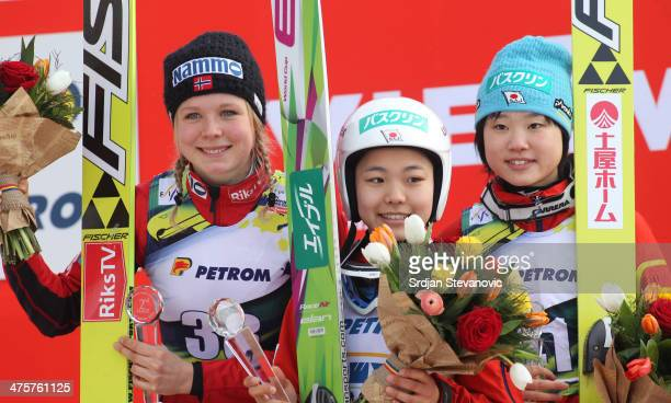 Second place Maren Lundby of Norway first place Sara Takanashi of Japan and third place Yuki Ito of Japan celebrate on the podium during medal...