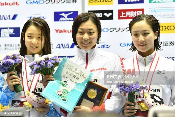 Second place Miho Teramura winner Satomi Suzuki and third place Kanako Watanabe celebrate on the podium at the medal ceremony for the Women's 50m...