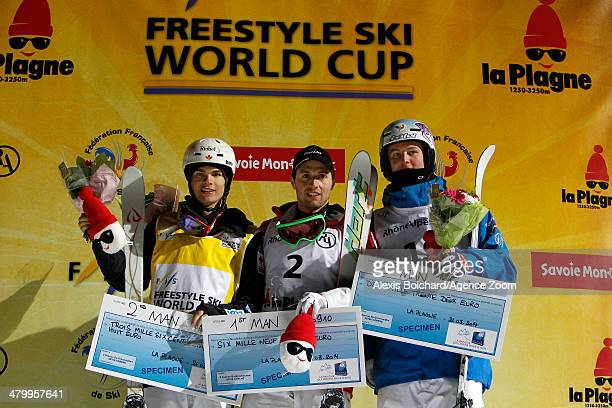 Second place Mikael Kingsbury of Canada first place Alex Bilodeau of Canada and third place Benjamin Cavet of France stand on the podium during the...