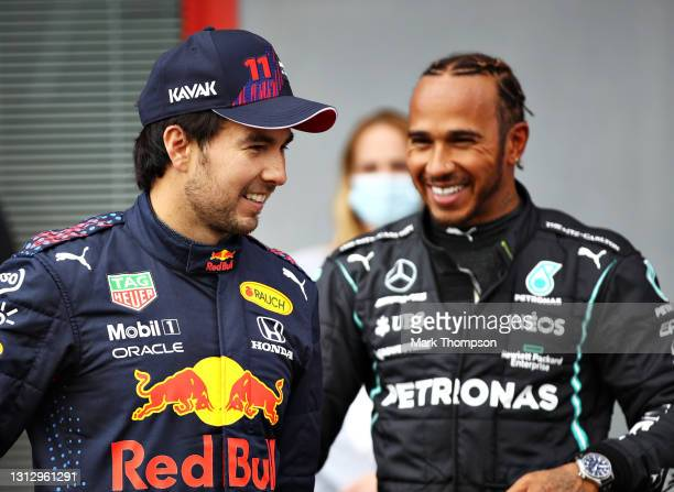 Second place qualifier Sergio Perez of Mexico and Red Bull Racing and pole position qualifier Lewis Hamilton of Great Britain and Mercedes GP talk in...