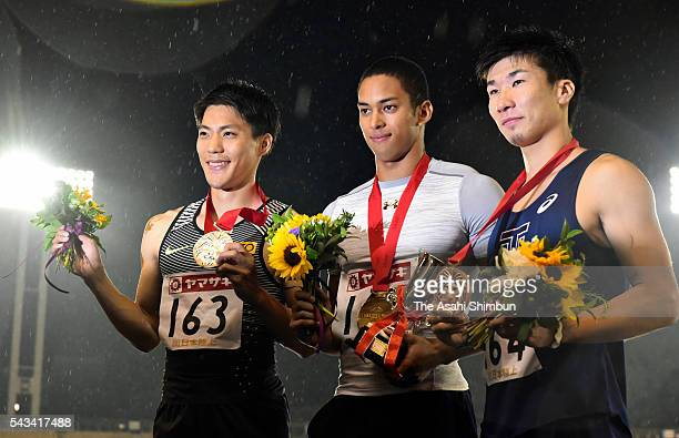 Second place Ryota Yamagata winner Asuka Cambrige and third place Yoshihide Kiryu pose on the podium at the medal ceremony for the Men's 100m during...