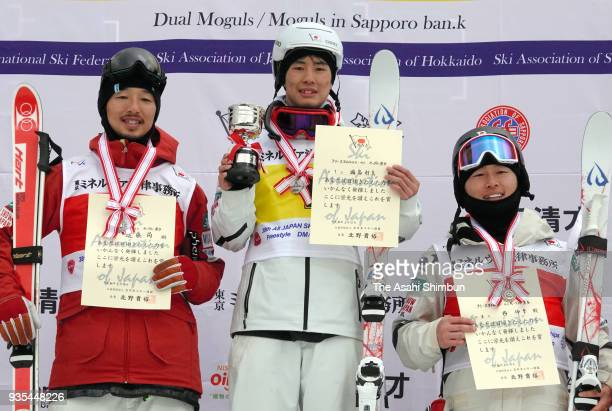 Second place Sho Endo winner Ikuma Horishima and third place Nobuyuki Nishi pose on the podium at the medal ceremony for the Men's Mogul on day two...