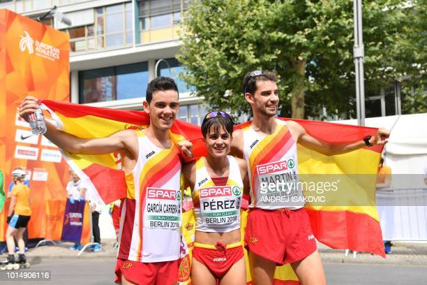 Second place Spain's Diego Garcia Carrera winner Spain's Maria Perez and winner Spain's Alvaro Martin pose with the national flag for photographers...
