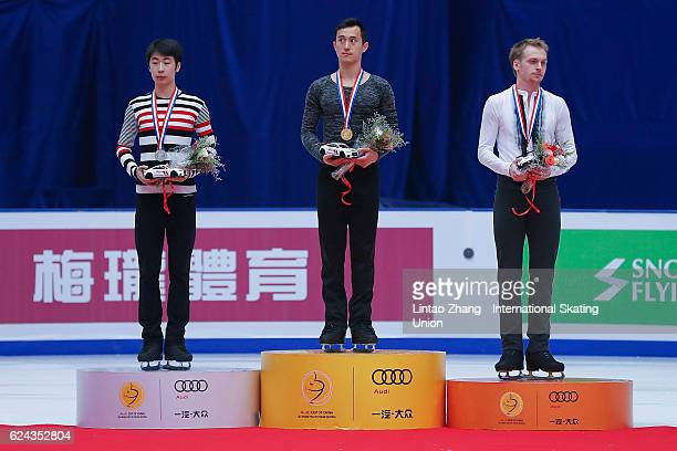 Second place winner Jin Boyang of China First place winner Patrick Chan of Canada Third place winner Sergei Voronov of Russia pose on the podium...
