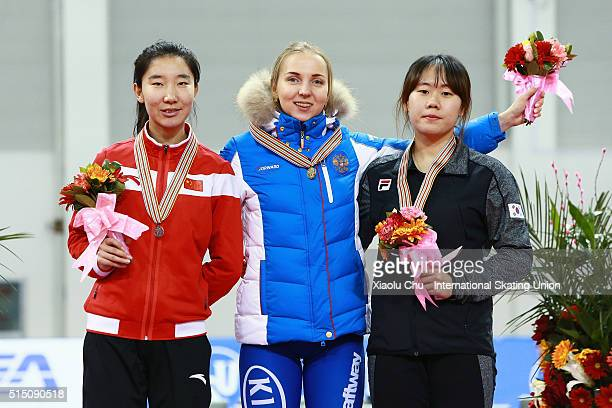 Second place winner Mei Han of China first place winner Elizaveta Kazelina of Russia and third place winner Ji Woo Park of Korea pose for photo on...