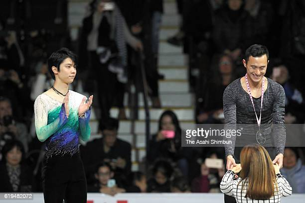 Second place Yuzuru Hanyu of Japan celbrates first place Patrick Chan of Canada on the podium at the medal ceremony for the Men's Singles during day...