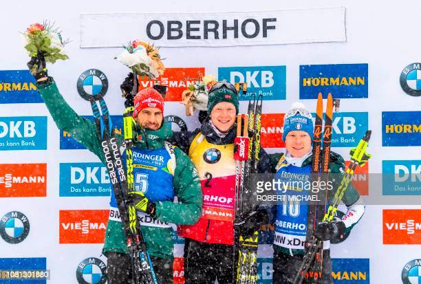 Second placed Arnd Peiffer of Germany winner Johannes Thingnes Boe of Norway and third placed Lukas Hofer of Italy pose on the podium after the men's...