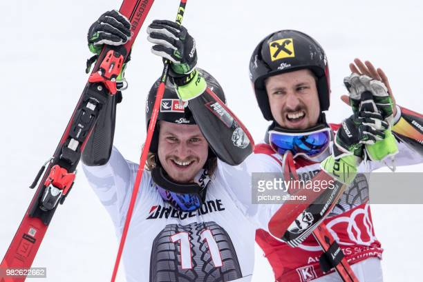Second placed Austrian Manuel Feller and winner Marcel Hirscher from Austria cheer after the giant slalom competition at the FIS Alpine Ski World Cup...