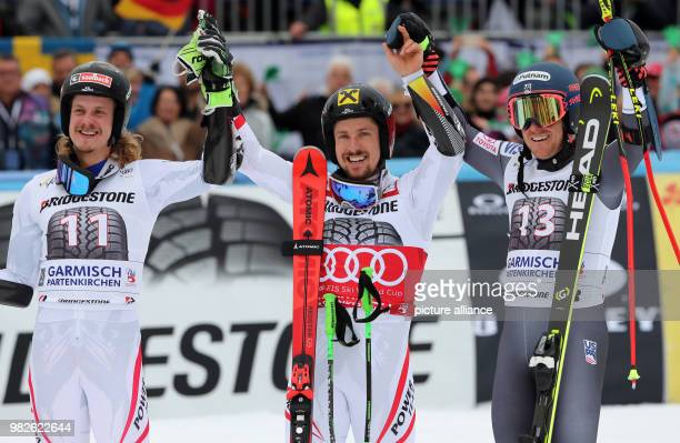 Second placed Austrian Manuel Feller winner Marcel Hirscher from Austria and American Ted Ligety who took third place cheer during the award ceremony...