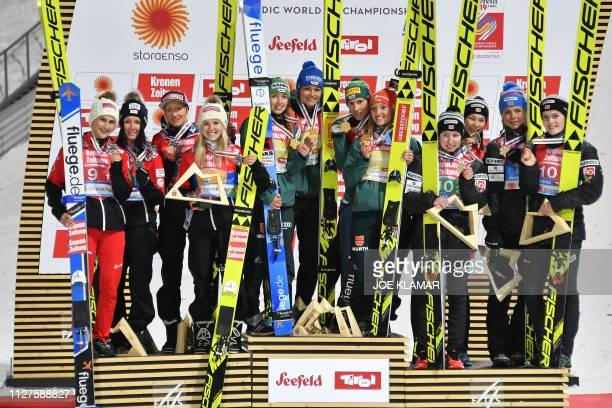 Second placed Austrian team, Germany's winning team and third placed team of Norway celebrate with their medals on the podium after the Ladies team...