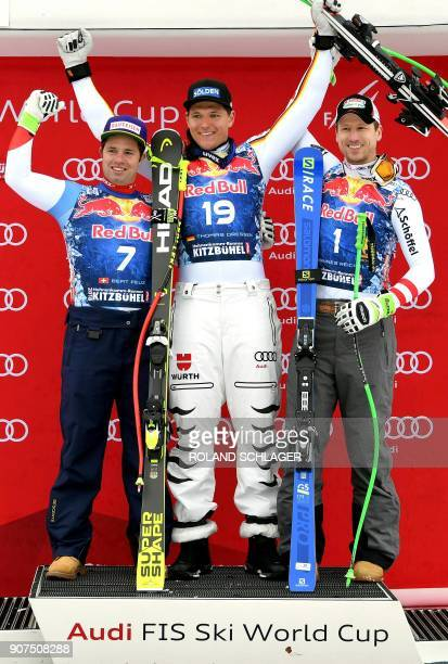 Second placed Beat Feuz of Switzerland winner Thomas Dressen of Germany and third placed Hannes Reichelt of Austria celebrate on the podium after...
