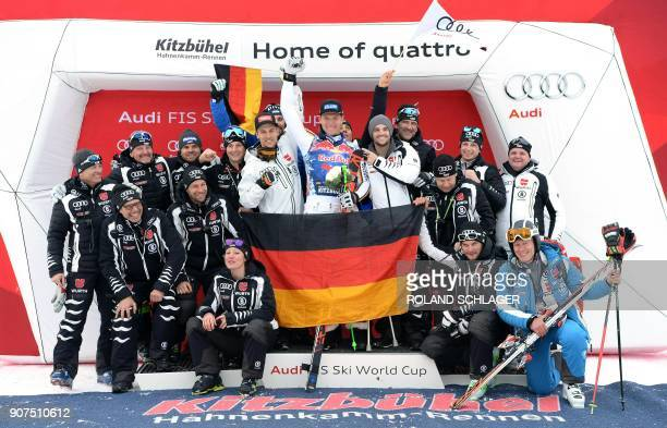 Second placed Beat Feuz of Switzerland winner Thomas Dressen of Germany and third placed Hannes Reichelt of Austria pose on the podium with members...