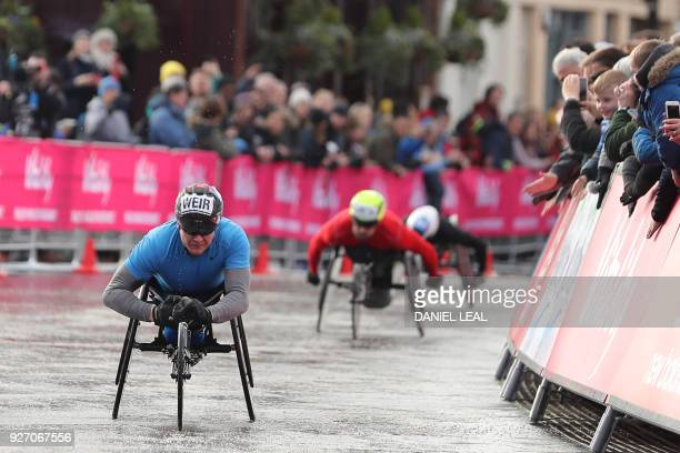 Second placed Britain's David Weir and third placed Britain's John Smith approach the finish line of the men's elite wheelchair race during the...