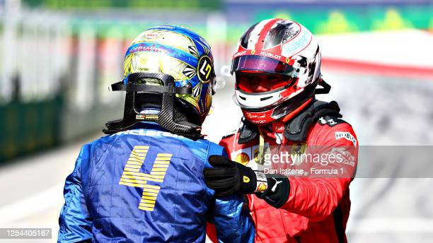Second placed Charles Leclerc of Monaco and Ferrari and third placed third placed Lando Norris of Great Britain and McLaren F1 celebrate in parc...