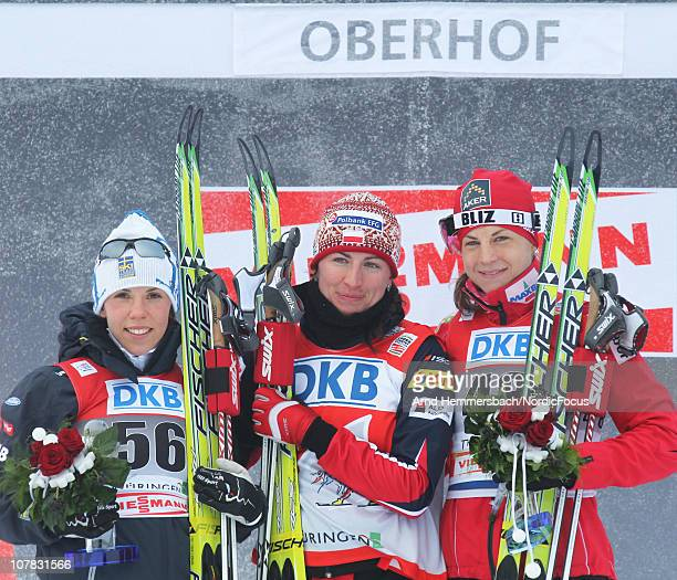 Second placed Charlotte Kalla of Sweden winner Justina Kowalczyk of Poland and third placed Astrid Uhrenholdt Jacobsen of Norway pose after the...