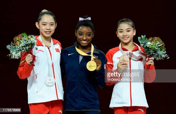Second placed China's Liu Tingting, first placed USA's Simone Biles and third placed China's Li Shijia celebrate on the podium after the beam...